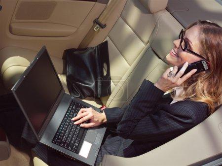 Photo pour Femme d'affaires a un ventilateur avec ordinateur portable en voiture noire - image libre de droit