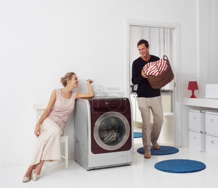 Photo for Housework, young woman and man doing laundry - Royalty Free Image