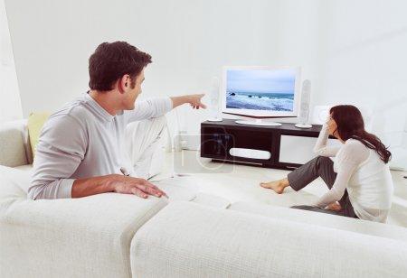 Photo pour Heureux couple assis sur canapé et regarder la télévision ensemble - image libre de droit