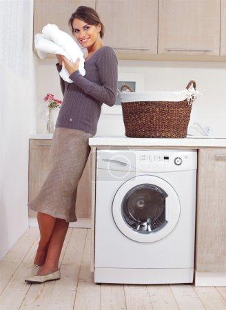 Woman on washing machine in kitchen...