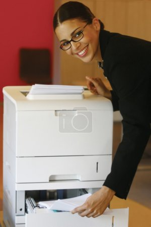 Photo for Pretty young businesswoman using Xerox machine at the office - Royalty Free Image