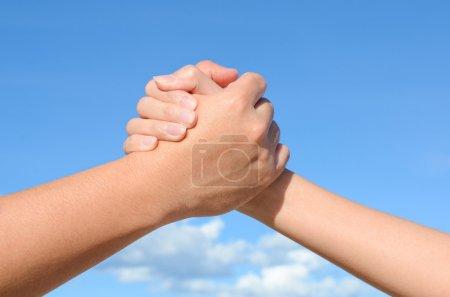 Photo pour Main partenaire entre un homme et une femme sur fond bleu ciel, Travail d'équipe - image libre de droit