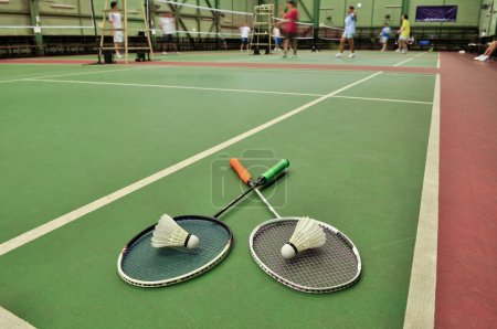 Badminton - two shuttlecocks on rackets in the badminton courts