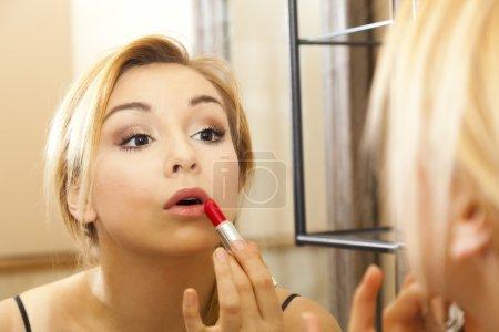 Beautiful woman doing makeup on her face