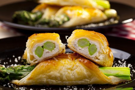 Photo for Asparagus baked in puff pastry served on black plate - Royalty Free Image