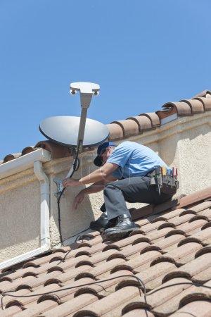 Foto de Instalación de satélite plato sistema de televisión en Español cubierta de teja. - Imagen libre de derechos