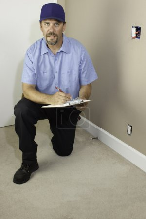Service man kneeling with clipboard