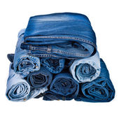 Lot of different blue jeans in the stack isolated on white background