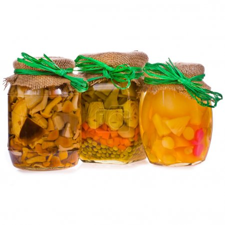 Three glass jars with preserves, pickled mushrooms, vegetables and stewed fruit