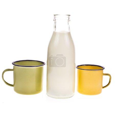 Bottle full of milk and yellow enamel mug