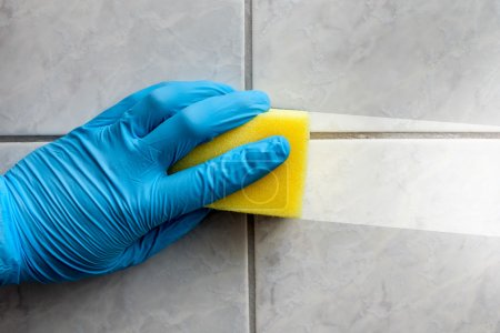 Photo for Cleaning sponge held in hand while cleaning bathroom - Royalty Free Image