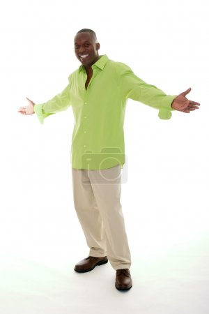 Photo for Casual young African American man standing in a bright green shirt with a welcoming hands apart gesture. - Royalty Free Image