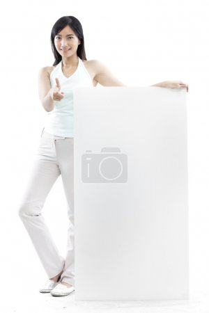 Casual woman standing behind a blank board on white background (green concept)