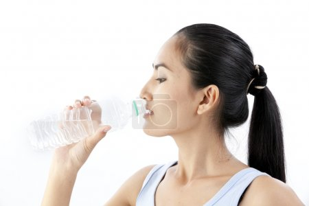 Sporty woman drinking water, isolated against white background
