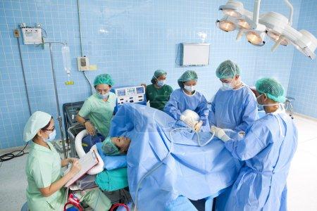 Photo pour Médecin en salle d'opération avec son équipe - image libre de droit