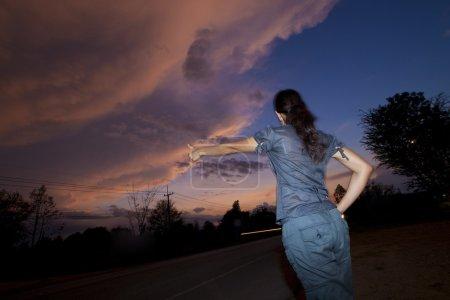 Woman wait on roadside at sunset