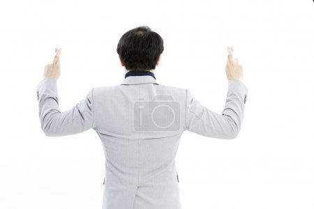 Superstitious - entrepreneur with crossed fingers over white background