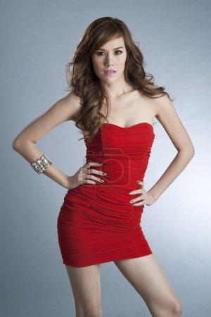 Photo pour Femme mince sexy en robe rouge sur fond gris - image libre de droit