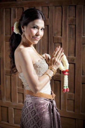 Photo pour Superbe femme asiatique en robe thaïlandais priant - image libre de droit