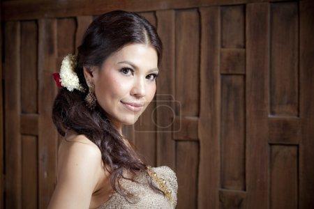 Photo pour Superbe femme asiatique en robe thaïlandais près de la paroi en bois - image libre de droit