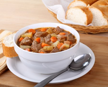 Photo for Bowl of vegetable beef soup with sliced bread - Royalty Free Image