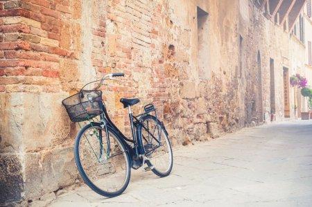 Photo pour Vélo vintage noir gauche dans une rue à pienza, en Toscane, Italie - image libre de droit
