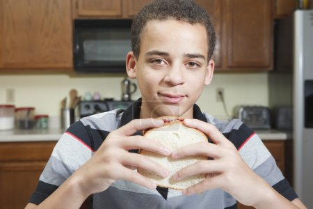 Teenager eating Peanut Butter and Jelly Sandwich