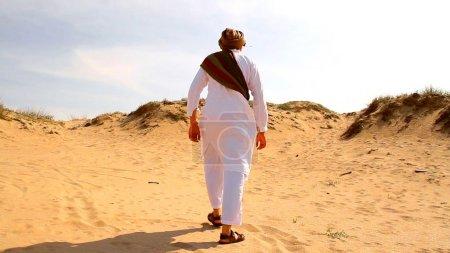 Photo pour Moyen-orientale homme marchant dans le désert pour atteindre concept de sauvetage - image libre de droit