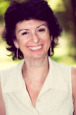 Woman in her 50s smiling outdoors portrait
