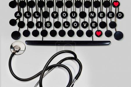 Photo pour Tout ce dont vous avez besoin est amour écrit sur un clavier vintage sur gris avec stéthoscope - image libre de droit