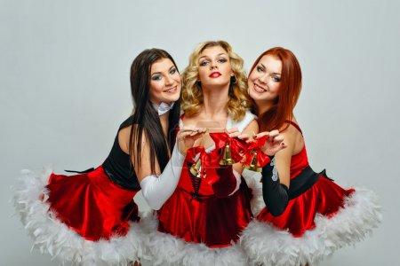 Photo pour Attrayant jeunes femmes en costumes de carnaval et cloches de Noël - image libre de droit