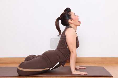Woman doing yoga exercise called Simha-asana ,The Lion Posture