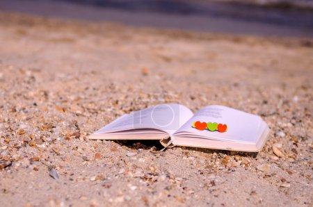 Photo pour Petits coeurs sont placés sur un livre de poésie ouvert à la plage, au cours de l'après-midi dans une période estivale de vacances - image libre de droit