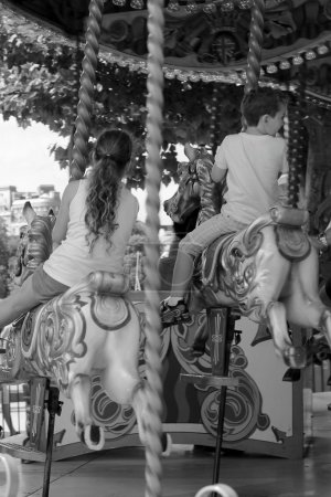 Vintage carousel merry-go-round painted horses with young children laughing