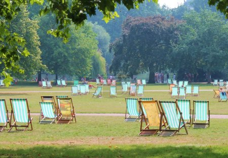 Striped deck chairs in park on grass