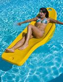 Dívka relaxaci v bazénu na plovoucí matraci