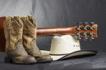 Photo for A close shot of a pair of boots. cowboy hat and a guitar handle. - Royalty Free Image