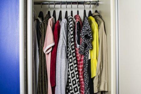 Photo pour Vêtements sur cintres dans le vestiaire de la maison - image libre de droit