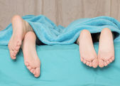 Feet of children lying on the bed