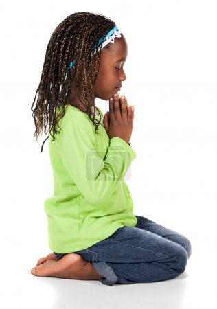Photo for Adorable small african child with braids wearing a bright green shirt and blue jeans. The girl is kneeling and praying. - Royalty Free Image