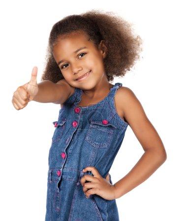 Foto de Adorable lindo niño africano con pelo afro con un vestido de mezclilla. la chica está mostrando un pulgar hasta la cámara. - Imagen libre de derechos