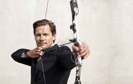 Businessman aiming bow and arrow