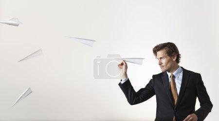 Businessman throwing paper airplanes at target