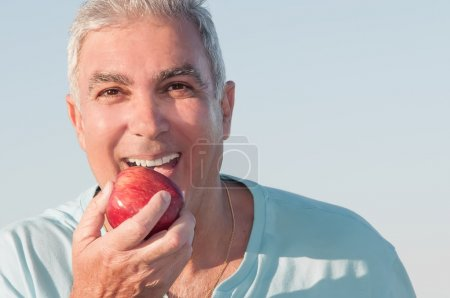 Photo for Closeup portrait of a senior man holding a red apple and smiling - Royalty Free Image