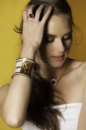 Portrait of brunette woman looking down wearing jewels