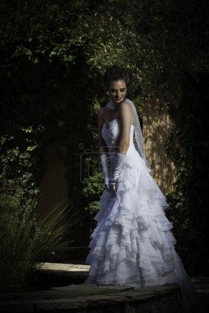 Beautiful bride posing next to courtyard fountain in strapless wedding dress