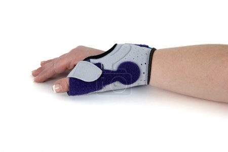 Wrist orthosis shown on a woman's hand.