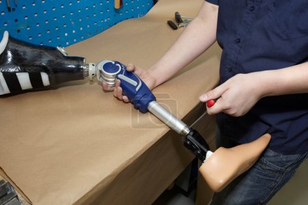 Photo for Worker in orthopaedic workshop adjusts leg prosthesis. - Royalty Free Image
