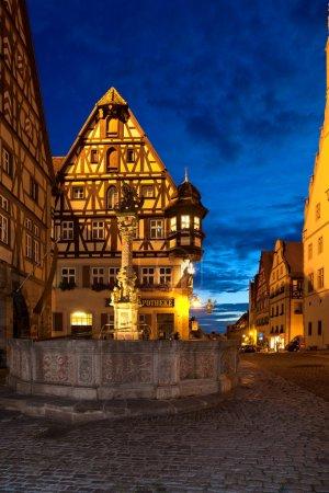 Photo pour Vue du marché de Rothenburg ob der Tauber dans la Herrngasse. En face de la fontaine médiévale St. Georgs - image libre de droit