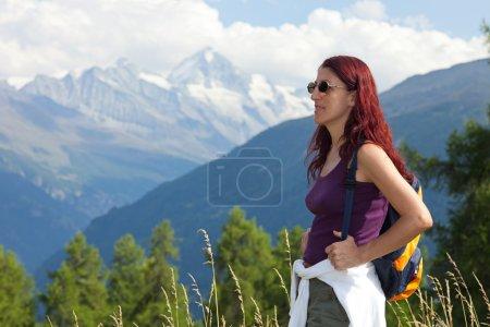 Photo pour Jolie jeune femme randonneuse portant des lunettes de soleil et un petit sac à dos debout dans un paysage alpin . - image libre de droit